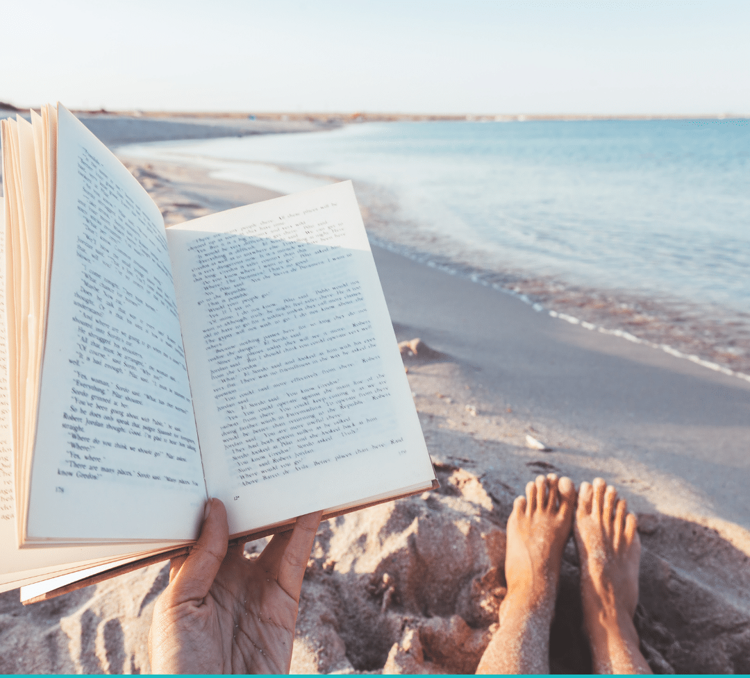 Person reading on the beach summer reading for teachers and tutors